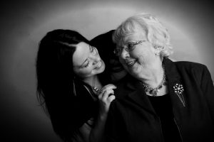 Photo: A young woman cheerfully leans in over the shoulder of a happy elderly woman. They are smiling at each other.