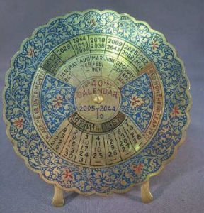 a brass calendar composed of rotating wheels