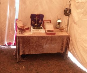 Photo of various artifacts displayed on draped tables with informational signs