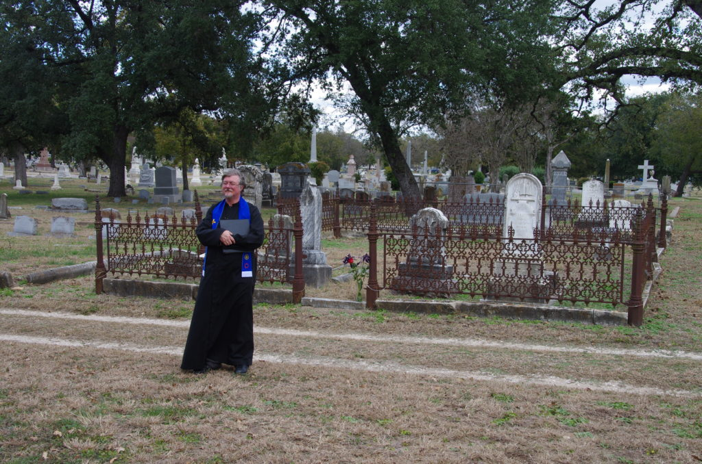 Saul, dressed in his clerical robe, stands in a cemetary