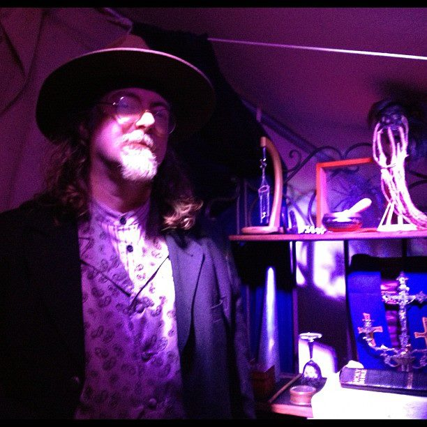 Saul Ravencraft stands next to his haunted artifacts